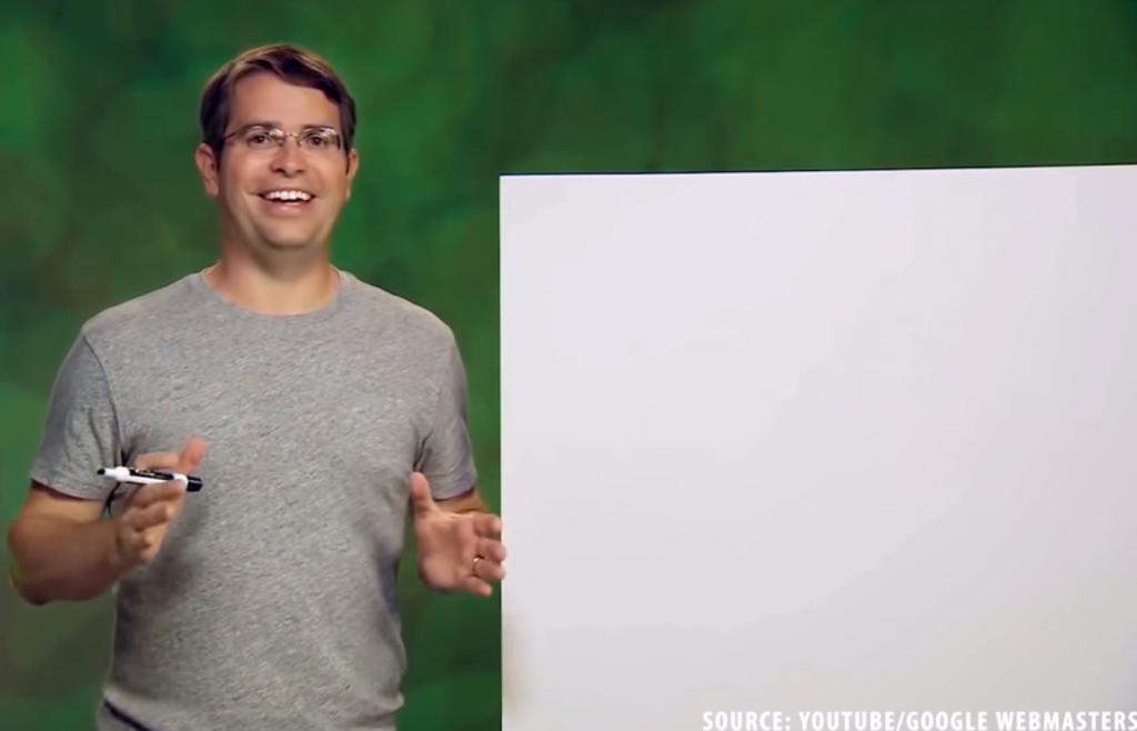 Still from SEO: The Movie showing Matt Cutts holding a whiteboard marker next to a blank whiteboard, mid-explanation of a concept. The credit in the bottom right corner reads 'Source: YouTube/Google Webmasters'.